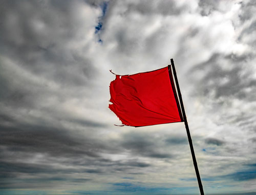 torn red flag against grey clouds | Colorado red flag law